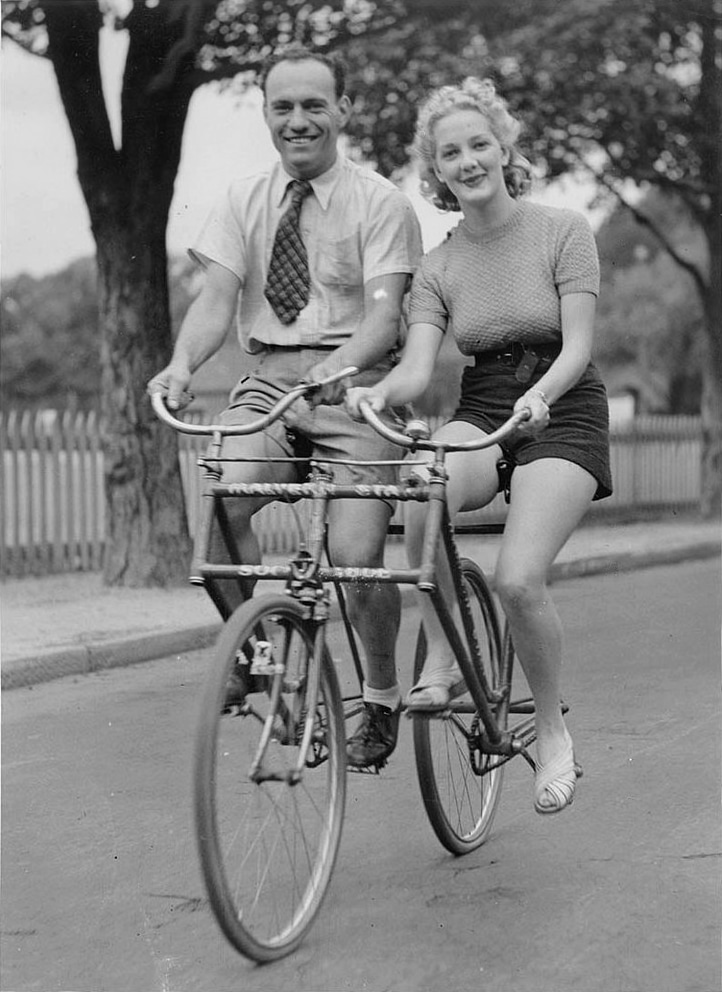 Man_and_woman_on_a_Malvern_Star_abreast_tandem_bicycle,_c._1930s,_by_Sam_Hood, State Library of Australia, Public Domain.jpg