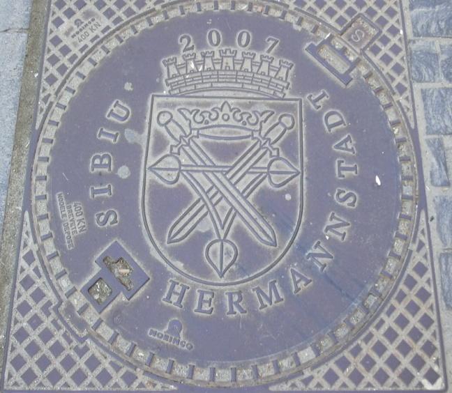 Rumänien, Hermannstadt_zweisprachiger_Kanaldeckel, 2007, Wolfgang J. Kraus, CC BY-Sa 3.0.JPG